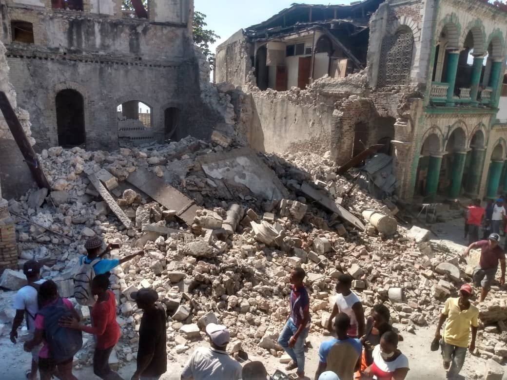 People walk through rumbles after the earthquake